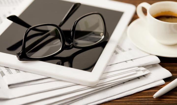 Kranten, tablet met bril op en koffie